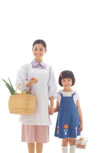 買い物帰りの割烹着のお母さんとおかっぱの女の子の写真素材 [FYI02029515]