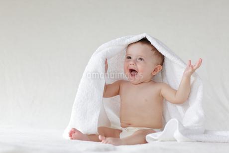 お座りをして頭にタオルをかけている外国人の赤ちゃんの写真素材 [FYI02029583]