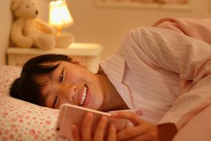ベッドで携帯を見て夜更かしする女の子の写真素材 [FYI02029601]