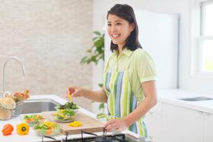 明るいキッチンで料理をする女性の写真素材 [FYI02029613]