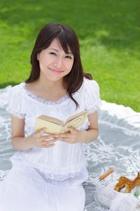 芝生で読書をする若い女性の写真素材 [FYI02029622]