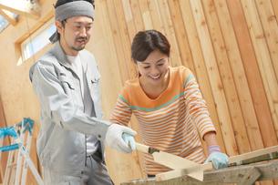 大工さんに作業を習う女性の写真素材 [FYI02029631]