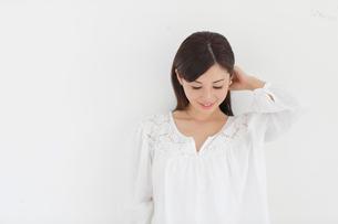 白い壁の前でポーズをとる女性の写真素材 [FYI02029641]