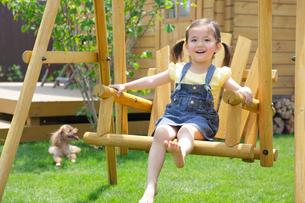 庭でブランコで遊ぶ女の子の写真素材 [FYI02029672]