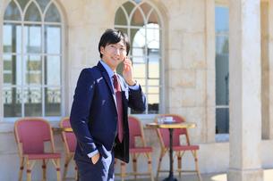 電話をしながらカフェの前を歩くビジネスマンの写真素材 [FYI02029680]