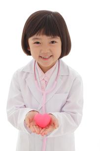 ピンクのハートを抱える白衣の女の子の写真素材 [FYI02029692]