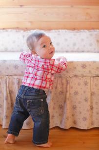 ベッドにつかまり立ちする赤ちゃんの写真素材 [FYI02029706]