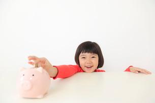貯金箱にお金を入れるおかっぱの女の子の写真素材 [FYI02029707]