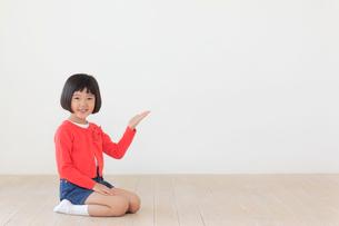 正座をして案内するおかっぱの女の子の写真素材 [FYI02029713]
