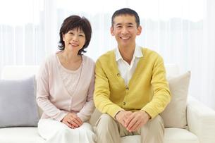 ソファーに座るシニアの夫婦のポートレートの写真素材 [FYI02029733]