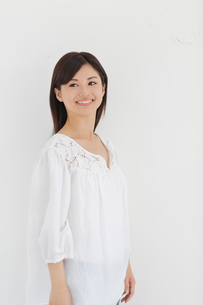 白い壁の前で微笑む女性の写真素材 [FYI02029735]