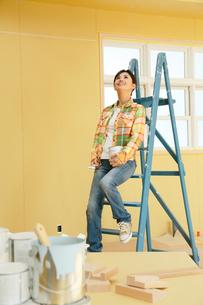 建築現場でペンキ缶を持ち室内を眺める女性の写真素材 [FYI02029739]
