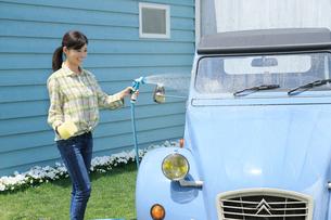 水色の可愛い自動車を洗車する女性の写真素材 [FYI02029778]