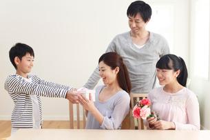 母の日のプレゼントを贈る子どもたちと見守るお父さんの写真素材 [FYI02029779]