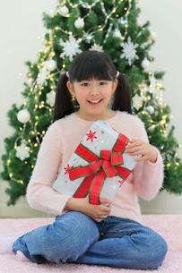クリスマスツリーのある部屋でくつろぐ女の子の写真素材 [FYI02029817]