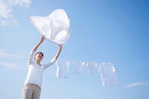 青空の下で家族の洗濯物を干す女性の写真素材 [FYI02029833]