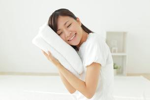 タオルに頬ずりする若い女性の写真素材 [FYI02029875]