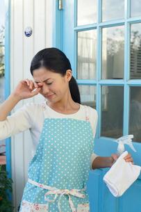 家事をしながら目をこする主婦の写真素材 [FYI02029912]