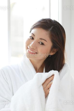 入浴後に窓辺で髪を乾かす女性の写真素材 [FYI02029944]
