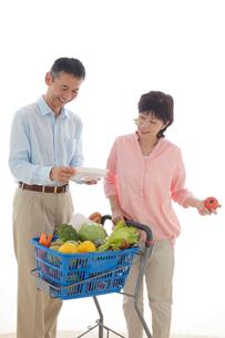 ショッピングカートを押しながら買い物をするシニアの夫婦の写真素材 [FYI02029949]