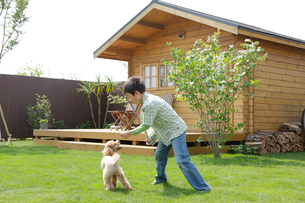 ログハウスの庭で遊ぶ男の子と犬の写真素材 [FYI02029953]
