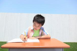 青空の下で勉強する男の子の写真素材 [FYI02029971]