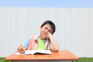 青空の下で勉強する男の子の写真素材 [FYI02029976]