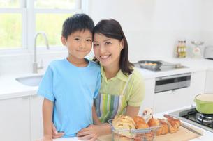 明るいキッチンに立つお母さんと子どもの写真素材 [FYI02030007]