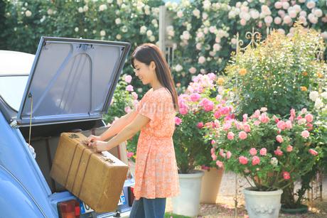 水色の可愛い車とスーツケースと若い女性の写真素材 [FYI02030015]