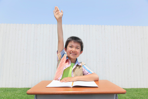 青空の下で勉強する男の子の写真素材 [FYI02030043]