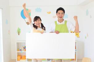 ホワイトボードを持つ男女の幼稚園の先生の写真素材 [FYI02030044]