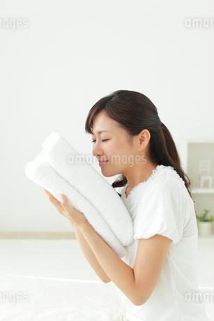 タオルに頬ずりする若い女性の写真素材 [FYI02030066]