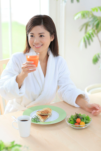 朝食を食べるバスローブ姿の女性の写真素材 [FYI02030068]