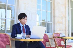 カフェで仕事をするビジネスマンの写真素材 [FYI02030075]
