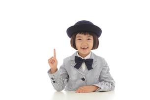 指さしポーズをする案内係の女の子の写真素材 [FYI02030078]