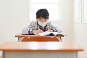 マスクをした体調不良の小学生と欠席の机の写真素材 [FYI02030079]