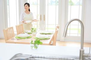 ダイニングキッチンでテーブルセッティングをする女性の写真素材 [FYI02030086]