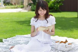 芝生で読書をする若い女性の写真素材 [FYI02030096]