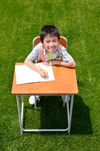 青空の下で勉強する男の子の写真素材 [FYI02030101]