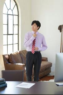 ネクタイを締めながら広いオフィスを歩くビジネスマンの写真素材 [FYI02030123]
