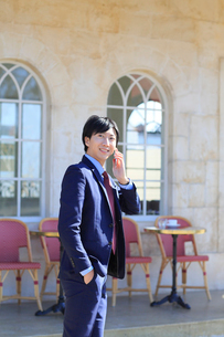 電話をしながらカフェの前を歩くビジネスマンの写真素材 [FYI02030133]
