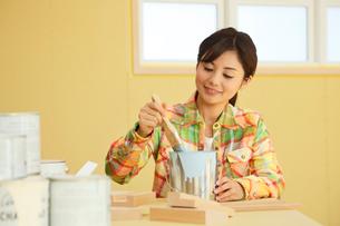 建築現場でペンキを混ぜる女性の写真素材 [FYI02030136]