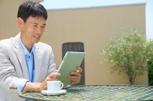 庭でコーヒーを飲みながらタブレットを触る中年男性の写真素材 [FYI02030143]