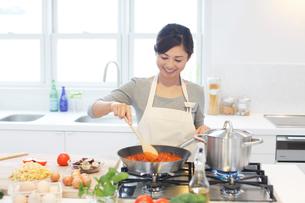 トマトソースを作る女性の写真素材 [FYI02030145]