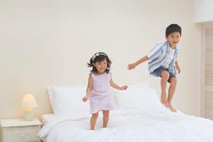 ホテルのベッドの上ではしゃぐ子どもたちの写真素材 [FYI02030148]