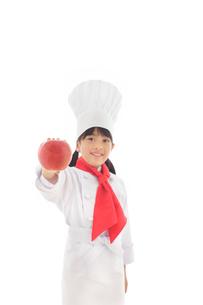 りんごを持つシェフの女の子の写真素材 [FYI02030164]