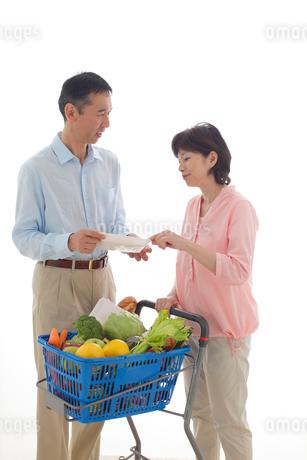 ショッピングカートを押しながら買い物をするシニアの夫婦の写真素材 [FYI02030170]