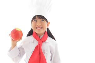 りんごを持つシェフの女の子の写真素材 [FYI02030202]