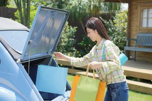 水色の可愛い車から買い物袋を出す若い女性の写真素材 [FYI02030203]