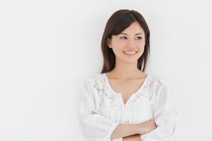 白い壁の前で微笑みながら考える女性の写真素材 [FYI02030207]
